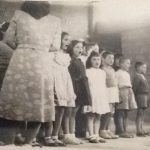 Miss Arshaluys Derderian standing backwards teaching songs to the students of the Aghpalian primary school of Chtaura Lebanon